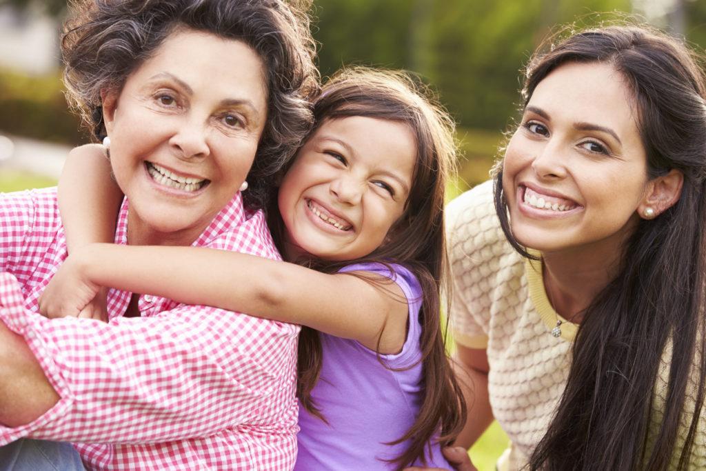 Abuela con su hija y su nieta en el parque sonriendo a la cámara
